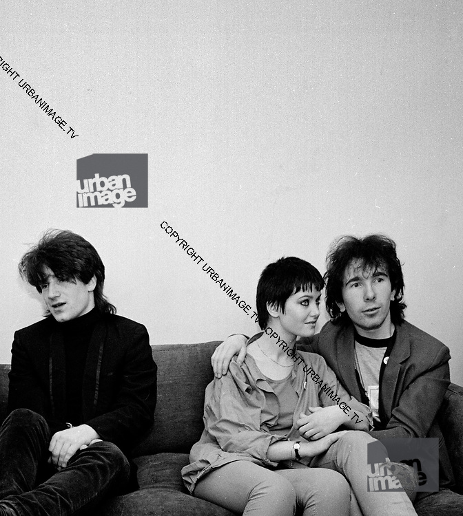 Photograph of U2 -  Bono. The Edge  and girlfriend back at the hotel -  USA tour 1981 Chicago  USA