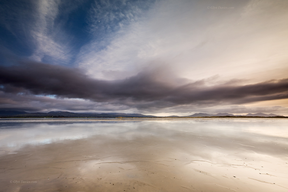 The Braint Estuary at Newborough at low tide. The sky was changing and high cirrus were becoming clouded by altostratus. Rain starts on the horizon. A half moon can be seen high in the frame.<br />