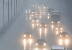 © Licensed to London News Pictures. 24/01/2018. Headley, UK. Cars and trucks drive with their lights on as wet and windy conditions hit the M25 in Surrey.  Photo credit: Peter Macdiarmid/LNP