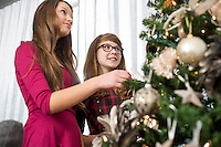 Siblings decorating on Christmas tree at home