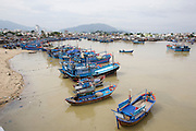 Fishing Harbour at the mouth of Cai River. Salting and drying fish. Trawlers.