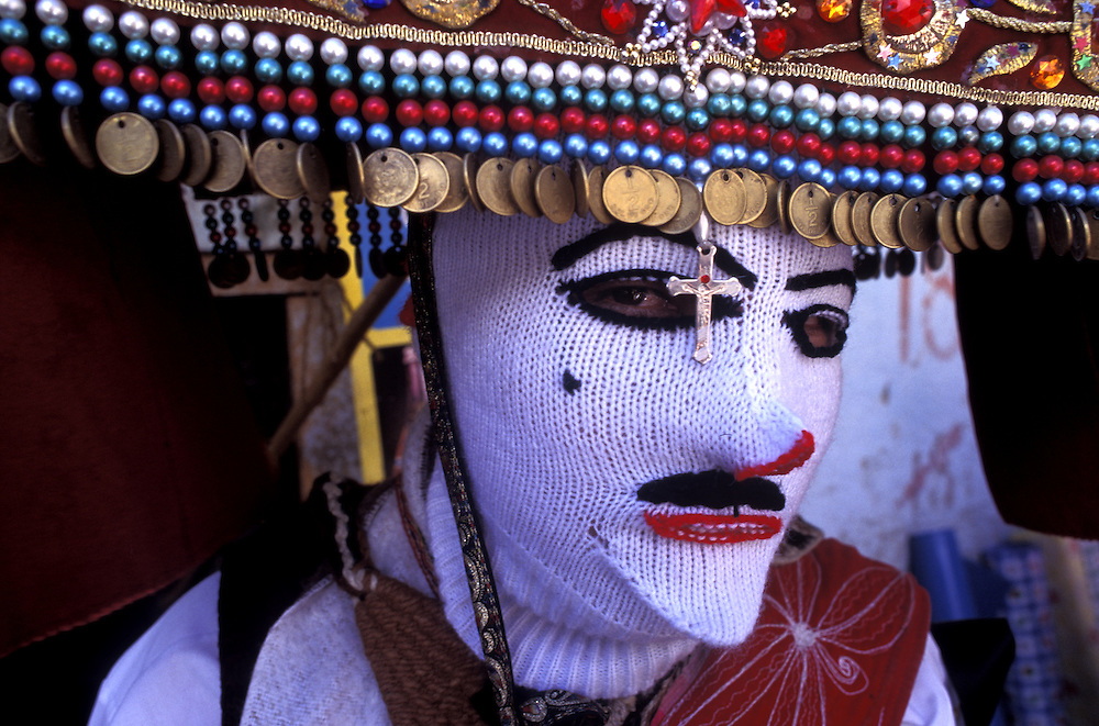 A dancer in traditional dress and white mask,a tradition mocking the conquistadors,at the festival of Corpus Christi in Paucartambo.