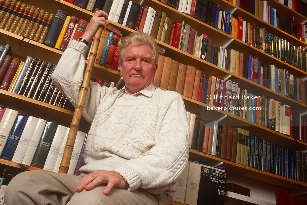 Surrounded by books is British Roman Catholic journalist, historian, speechwriter and author, Paul Johnson on 21st February 1992 in London England. Paul Bede Johnson (b1928) is an English journalist, historian, speechwriter and author. He was educated at the Jesuit independent school Stonyhurst College, and at Magdalen College, Oxford. Johnson first came to prominence in the 1950s as a journalist writing for, and later editing, the New Statesman magazine. A prolific writer, he has written over 40 books and contributed to numerous magazines and newspapers. While associated with the left in his early career, he is now a conservative popular historian.