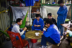 Chinese workers play card game at the dorm near the Haiphong Thermal Power Plant construction site in Trung Son, Vietnam, Nov. 22, 2009. At the construction site here, a few miles northeast of the port city of Haiphong, an entire Chinese world has sprung up, including four walled dormitory compounds for the Chinese workers, restaurants with Chinese signs advertising dumplings and fried rice, and currency exchange shops.