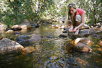 Young Woman Testing Water in Creek