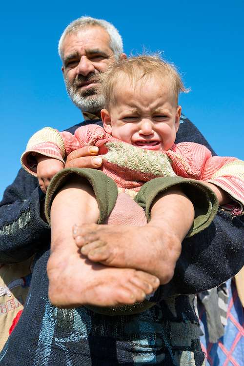A Syrian man holds a barefoot two-year-old child in Atmeh refugee camp in northern Syria, home to some 12,000 people displaced by the country's civil war. These two had fled the city of Jisr al Shughour five months earlier and said they were struggling for basics, including shoes for the young children.