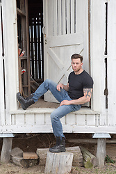 muscular man sitting by a rustic barn