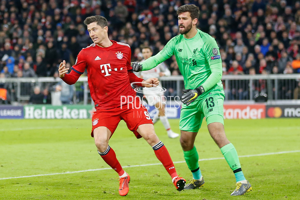 Liverpool goalkeeper Alisson Becker (13) holds off Bayern Munich forward Robert Lewandowski (9) during the Champions League match between Bayern Munich and Liverpool at the Allianz Arena, Munich, Germany, on 13 March 2019.