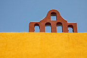 Terra cotta arches against a yellow wall on the Inmaculada Concepcion Church in San Miguel de Allende, Guanajuato, Mexico.