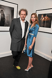MIKE FIGGIS and ANOUSHKA BECKWITH at a private view of an exhibition of photographs by Mike Figgis entitled 'Kate & Other Women' held at The Little Black Gallery, 13 A Park Walk, London SW10 on 22nd June 2011.