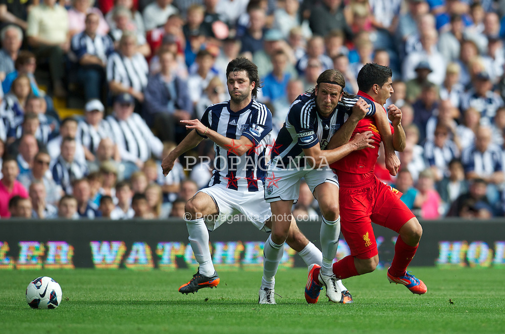 WEST BROMWICH, ENGLAND - Saturday, August 18, 2012: Liverpool's Luis Alberto Suarez Diaz is elbowed in the neck by West Bromwich Albion's Jonas Olsson during the opening Premiership match of the season at the Hawthorns. (Pic by David Rawcliffe/Propaganda)