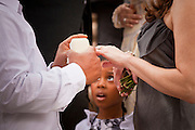 14 FEBRUARY 2012 - PHOENIX, AZ:    A girl watches her father slip a wedding ring on his bride's finger during a mass wedding in Phoenix Tuesday. Ninetysix couples got married in a mass ceremony on the steps of the Arizona Supreme Court to mark the Valentine's Day holiday. The wedding was also an occasion to mark Arizona's centennial of statehood.    PHOTO BY JACK KURTZ