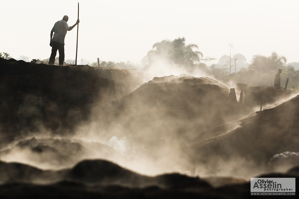 A man spreads sawdust on a large mound of charcoal at a wood charcoal production site on the outskirts of San Pedro, Bas-Sassandra region, Côte d'Ivoire on Sunday March 4, 2012. Men, women and children - who don't go to school - work here seven days a week.
