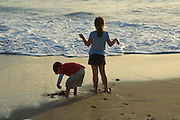 Kids on Beach playing in the sand by waterline.