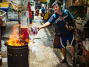 "17 AUGUST 2016 - BANGKOK, THAILAND: A man burns ""ghost money"" in front of his home during the Ghost Festival in the Chinatown section of Bangkok. The Ghost Festival is a Buddhist and Taoist holy day celebrated on the 15th day of the 7th lunar month. It is primarily celebrated in China and Chinese communities beyond China. In Thailand, it's celebrated in Thai-Chinese communities in Bangkok, Phuket and Chiang Mai.  On that day ghosts and spirits, including those of the deceased ancestors, come out from the lower realm to visit the living. Families prepare elaborate banquets for the spirits and burn ""ghost money"" for the spirits to use in the other realm. It is a day for venerating dead relatives.     PHOTO BY JACK KURTZ"