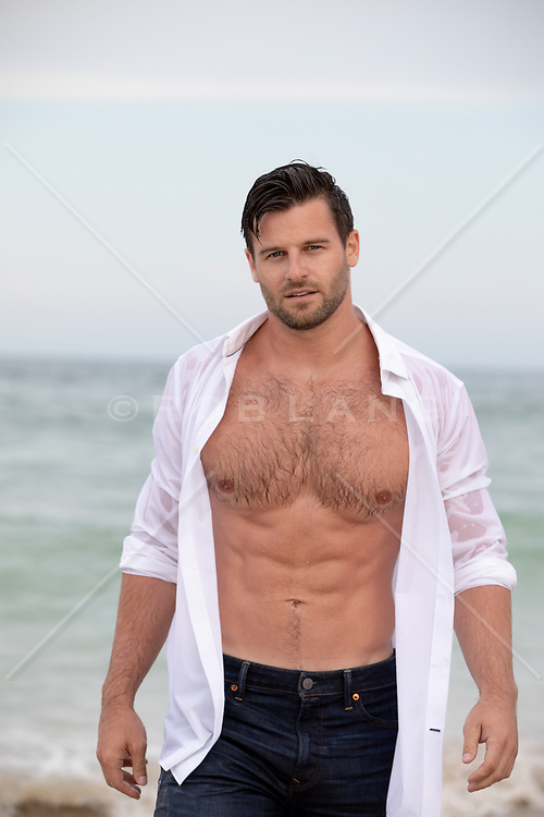 good looking All American man with an open shirt on the beach
