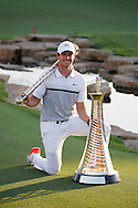 Rory McIlroy celebrates winning The Race To Dubai and The DP World Tournaments with the trophies on the 4th day