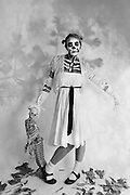 female full length shot with skeleton makeup holding skeleton shot in black and white on white background
