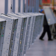 Long row of fabricated metal boxes with worker in background.