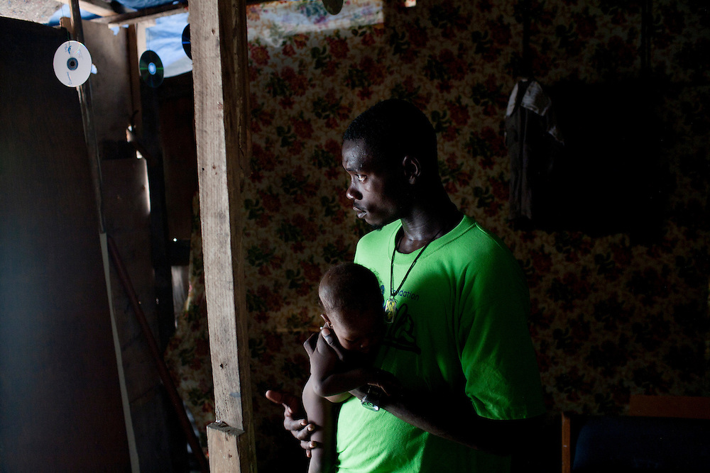 A man holds a friend's baby in the camp for people displaced by the earthquake on Champs de Mars, across from the destroyed national palace, on July 14, 2010 in Port-au-Prince, Haiti.