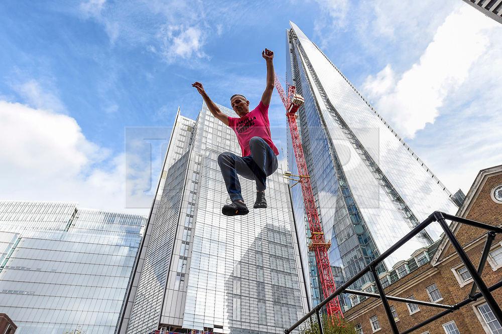 "© Licensed to London News Pictures. 10/10/2019. LONDON, UK. Alister O'Loughlin, a member of the Urban Playground Parkour Team, rehearses ""Zoo Humans"" in the courtyard of Guy's Hospital adjacent to The Shard building to kick of the Dance Umbrella 2019 festival.  The show is inspired by the shocking statistic that three quarters of young people in the UK spend less time outdoors than prisoners.   Photo credit: Stephen Chung/LNP"