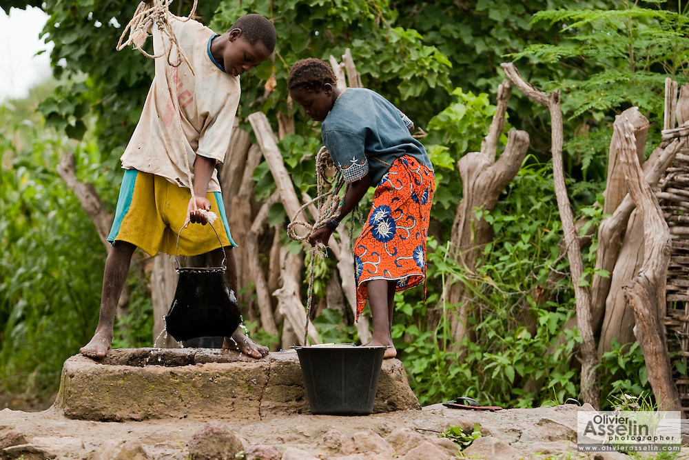Children pull water from a well in the village of Kabe, Mali on Monday August 30, 2010...