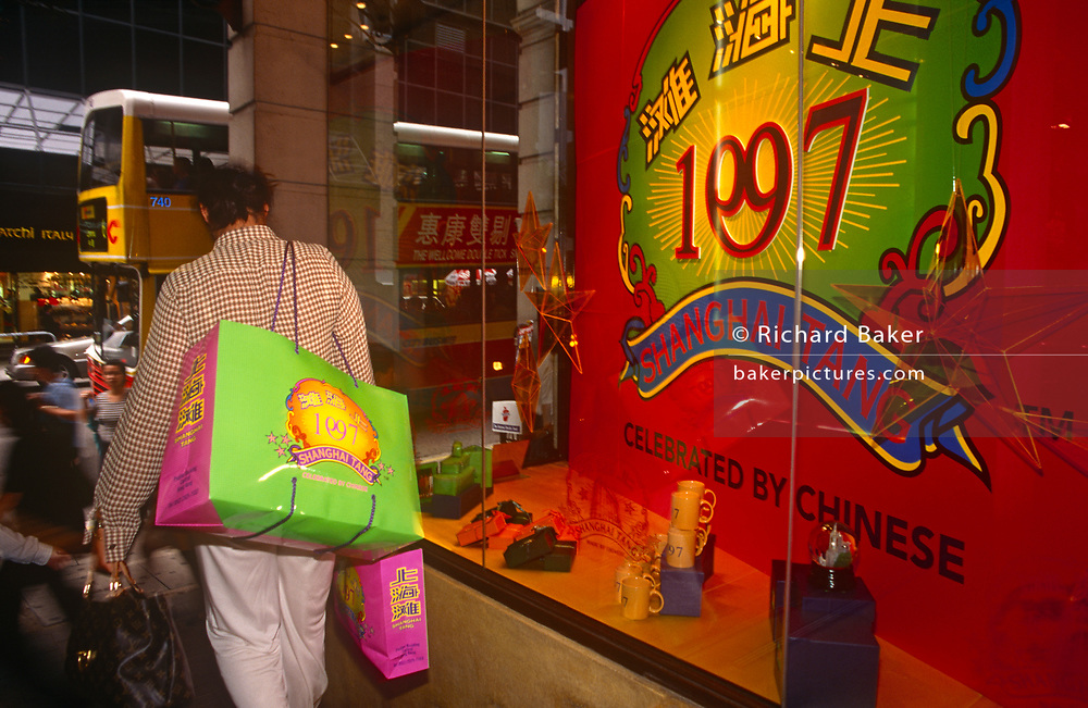 A shopper leaves the Shanghai Tang fashion store in Central, the day after the Handover of sovereignty from Britain to China, on 30th June 1997, in Hong Kong, China. Midnight signified the end of British rule, and the transfer of legal and financial authority back to China. Hong Kong was once known as 'fragrant harbour' (or Heung Keung) because of the smell of transported sandal wood.