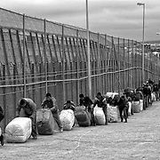 MELILLA, SPAIN - APRIL 21, 2010 : A group of  porters passing  next to the separation fence between Spain and Morocco at the  border of El Barrio Chino, where the porters  have to push or carry contraband packages that weigh 80 to 100 kg. on April 21 , 2010 in Melilla. Spain. Every day at the pedestrian border of El Barrio Chino hundreds of people are involved in transporting smuggled goods from Melilla a Spanish enclave on the North African coast to Morocco.For each package introduced in morocco receive between 3 an 5 euros depending on size,with a little luck achieved make three trips a day.It is estimated that from Monday to Thursday on foot enter Melilla 8.000 porters, mostly women, to return to Morocco with huge sacks of goods from the warehouse border area of Beni Enzar in Melilla .( Photo by Jordi Cami )