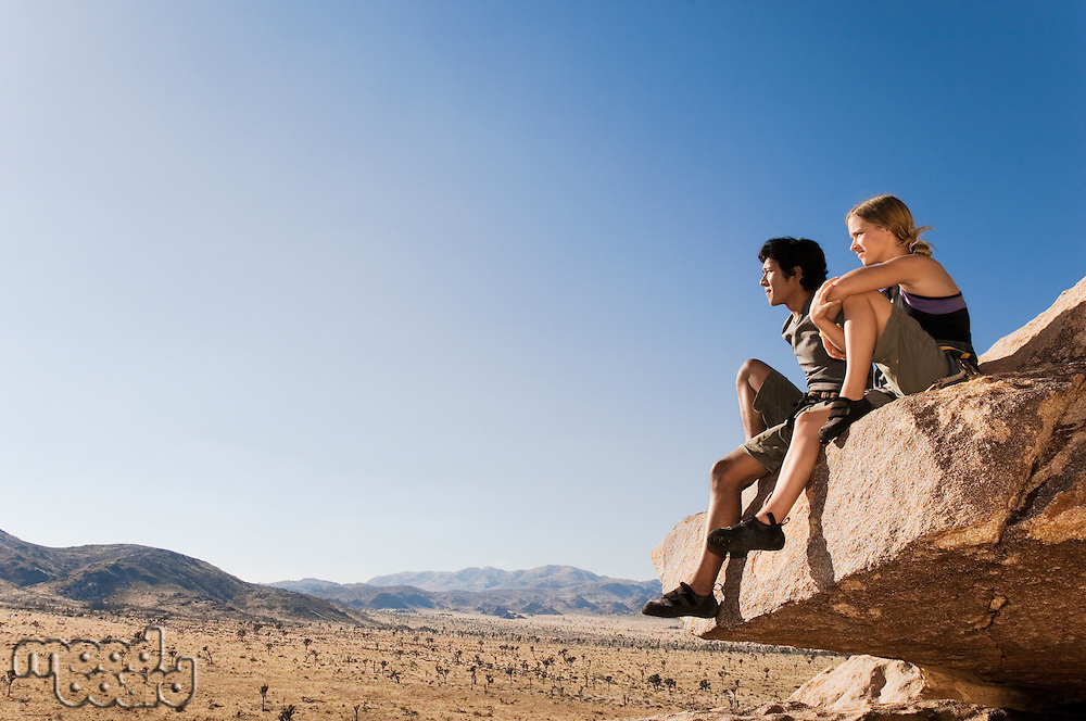 Climbers sitting on Rock Looking at Desert