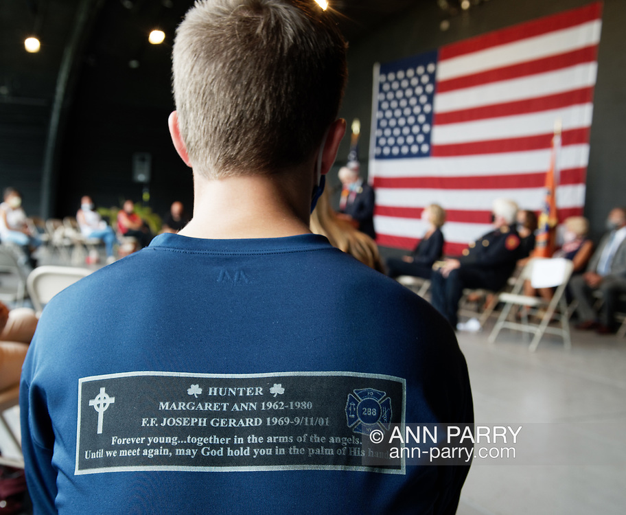 East Meadow, New York, U.S. September 10, 2020. JOEY LABO, 16, of Wantagh, seen from back sitting on stage during 9/11 event, wearing a shirt in memory of his uncle Joseph G. Hunter, a FDNY 288 firefighter who died during the attacks, 9/11/01. Nassau County commemorated 19th anniversary of September 11 terrorist attacks with Remembrance Ceremony at Eisenhower Park, with names read of 348 county residents killed that day.