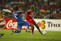 BANGKOK, THAILAND - Thailand. Thursday, July 24, 2003: Liverpool's Emile Heskey gets away from Thailand's Jukkapant Punpee to score the opening goal during a preseason friendly match at the Rajamangala National Stadium. (Pic by David Rawcliffe/Propaganda)
