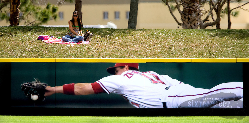 The Washington Nationals defeated the Baltimore Orioles in a spring training game 5-4, Thursday, March 19, 2009, in Viera, FL.  A fan sits on the berm behind the left field wall and watches the game.  (AP Photo/Gary Cosby Jr.)