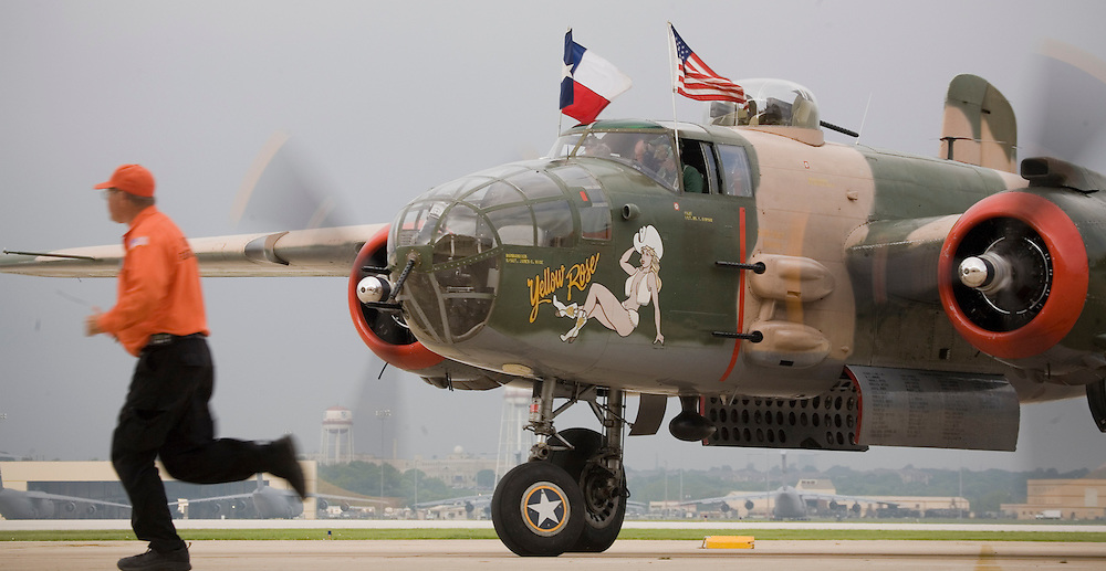 "The crew of the ""Yellow Rose"" B-25J Mitchell bomber from the Yellow Rose Squadron of the Commemorative Air Force (CAF) starts it's engines and takes off from Kelly Field and pass by the C-5 Galaxy aircraft of the 433rd Airlift Wing on April 20, 2007. Three North American B-25 Mitchell bombers of the CAF were viewed by military families at Kelly Field, Lackland Air Force Base, TX on April 20, 2007. After the viewing, the three bombers made a 3-ship formation flyby of the Basic Military Training airmen graduation ceremonies. the aircraft were at Lackland Air Force Base to commemorate the 65th anniversary of the Doolittle air raid of Tokyo, Japan, the surviving airmen were present for a reunion during the week. (Photo copyright 2007 Lance Cheung)..The pilot and mechanic of the ""Miss Mitchell"" use team work to safely start the B-25J Mitchell bomber from the St.Paul, Minnesota Wing of the Commemorative Air Force (CAF). Three North American B-25 Mitchell bombers of the CAF were viewed by military families at Kelly Field, Lackland Air Force Base, TX on April 20, 2007. After the viewing, the three bombers made a 3-ship formation flyby of the Basic Military Training airmen graduation ceremonies. the aircraft were at Lackland Air Force Base to commemorate the 65th anniversary of the Doolittle air raid of Tokyo, Japan, the surviving airmen were present for a reunion during the week. (Photo copyright 2007 Lance Cheung).."