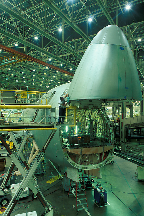 USA, Washington, Everett, Engineer works on swinging nose of Boeing 747 cargo jet inside construction hangar