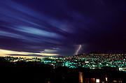 City lights at twighlight with lighning bolt and blurred cloud streaks
