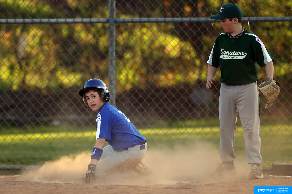 A young baseball player steals third base during the Norwalk Little League baseball competition at Broad River Fields,  Norwalk, Connecticut. USA. Photo Tim Clayton