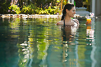 Young woman holding drink in natural swimming pool portrait