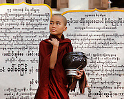 Novice monk collecting morning alms. Mandalay, Myanmar.
