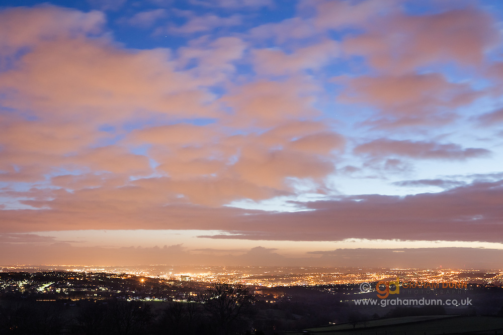 City lights illuminate the clouds over the city of Sheffield at night. Light pollution at its best! Captured in South Yorkshire from the boundary of the Peak District. England, UK. January, 2016