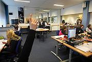"""Nederland, Weert, 20-12-2007..VMBO school """"het Kwadrant"""". In een ruimte die ingericht is als kantoor leren leerlingen op een afdeling administratie te werken. Een scholier steekt haar vinger in de lucht om iets te vragen aan de docent...Foto: Flip Franssen/Hollandse Hoogte"""