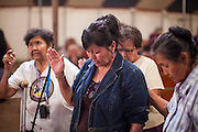 "12 JULY 2012 - FT DEFIANCE, AZ:      People pray during the alter call at the 23rd annual Navajo Nation Camp Meeting in Ft. Defiance, north of Window Rock, AZ, on the Navajo reservation. Preachers from across the Navajo Nation, and the western US, come to Navajo Nation Camp Meeting to preach an evangelical form of Christianity. Evangelical Christians make up a growing part of the reservation - there are now more than a hundred camp meetings and tent revivals on the reservation every year. The camp meeting in Ft. Defiance draws nearly 200 people each night of its six day run. Many of the attendees convert to evangelical Christianity from traditional Navajo beliefs, Catholicism or Mormonism. ""Camp meetings"" are a form of Protestant Christian religious services originating in Britain and once common in rural parts of the United States. People would travel a great distance to a particular site to camp out, listen to itinerant preachers, and pray. This suited the rural life, before cars and highways were common, because rural areas often lacked traditional churches.PHOTO BY JACK KURTZ"