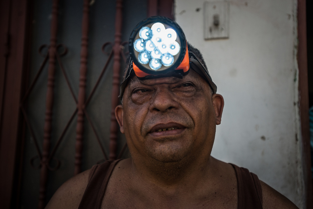 """MARACAY, VENEZUELA - MARCH 21, 2016:  José Sánchez, 56, shows a visiting journalist the battery-operated headlamp he bought,  to be able to see inside his home when the electricity is shut off during state-mandated rationing.  Venezuela is shutting down this week, as the government struggles with a deepening electricity crisis.  President Nicolas Maduro gave everyone an extra three days off work, extending the two-day Easter holiday, according to a statement in the Official Gazette published late last Tuesday.  The government has rationed electricity and water supplies across the country for months and urged citizens to avoid waste as Venezuela endures a prolonged drought that has slashed output at hydroelectric dams. The ruling socialists have blamed the shortage on the El Nino weather phenomena and """"sabotage"""" by their political foes, while critics cite a lack of maintenance and poor planning.  PHOTO: Meridith Kohut for Bloomberg News"""