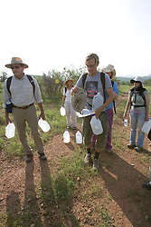 """Camp director Andrew """"Budge"""" Burridge (centre) prepares to take the group out on the morning patrol of the desert trails surrounding the No More Deaths camp in Southern Arizona. Each volunteer carries 2 4-litre jugs of water that is left along the trails for migrants passing through the area. The jugs are dated so the group has an idea of when people have travelled along a certain trail."""