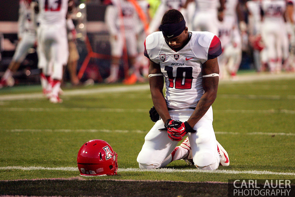 October 26th, 2013:  University of Arizona Wildcats freshman wide receiver Samajie Grant (10) on his knees for a pre game prayer before the start of action in the NCAA football game between the University of Arizona Wildcats and the University of Colorado Buffaloes at Folsom Field in Boulder, Colorado