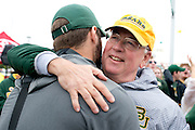 Judge Ken Starr, President and Chancellor of Baylor University, hugs members of the Baylor Bears football team as they exit the team bus before defeating #9 TCU in Waco, Texas on October 11, 2014. (Cooper Neill for The New York Times)