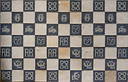 Tiled chequerboard floor, aerial view, in the Salle Capitulaire or Chapter House at Fontevraud Abbey, Fontevraud-l'Abbaye, Loire Valley, Maine-et-Loire, France. Among the tile patterns are the initials RB of Renee de Bourbon, 1494-1539, abbess of Fontevraud, and the Emblem of Fontevraud, a winged 'L' surmounted by the royal crown of Louise de Bourbon, Abbess of Fontevraud 1534-75. The Chapter House was built in the 16th century and its walls were painted in 1563 with frescoes of scenes from Christ's Passion by the Anjou artist Thomas Pot. The abbey itself was founded in 1100 by Robert of Arbrissel, who created the Order of Fontevraud. It was a double monastery for monks and nuns, run by an abbess. The abbey is listed as a historic monument and a UNESCO World Heritage Site. Picture by Manuel Cohen