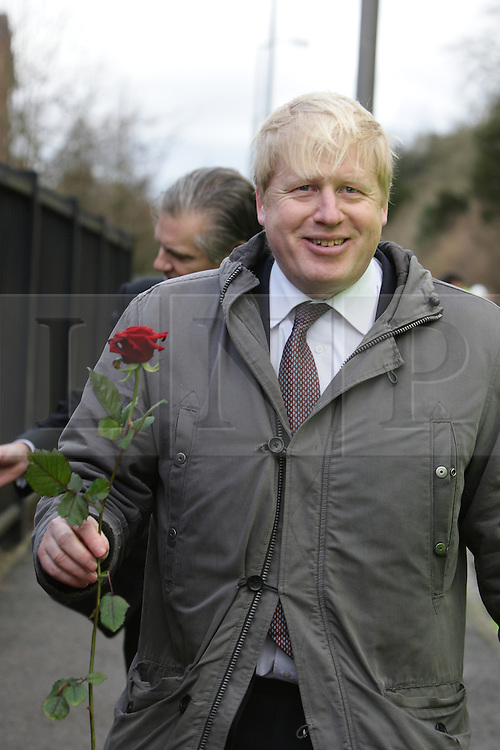 © Licenced to London News Pictures.  11/02/2014.  London UK  Mayor of London Boris Johnson visits the site of Kenley Water works in Godstone Road Kenley nr Purley Croydon. Flanked by members of the water works staff he toured the site and walked along the A22/ Godstone Road to see for himself the work being done He collects a rose from Marilyn Poulter who runs a flower shop affected.<br /> Photo Credit: Presspics/LNP