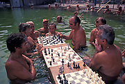 Hungarian gentlemen play chess in the thermal healing spa waters of Budapest's famous Szechenyi thermal bath, on 18th June 1990, in Budapest, Hungary. Budapest is especially known for its spas. The Széchenyi Medicinal Bath  (Szechenyi-gyogyfurdo) is the largest medicinal bath in Europe. Its water is supplied by two thermal springs, their temperature is 74°C/165°F and 77°C/171°F, respectively. The bath can be found in the City Park, and was built in 1913 in Neo-baroque style to the design of Gyozo Czigler.