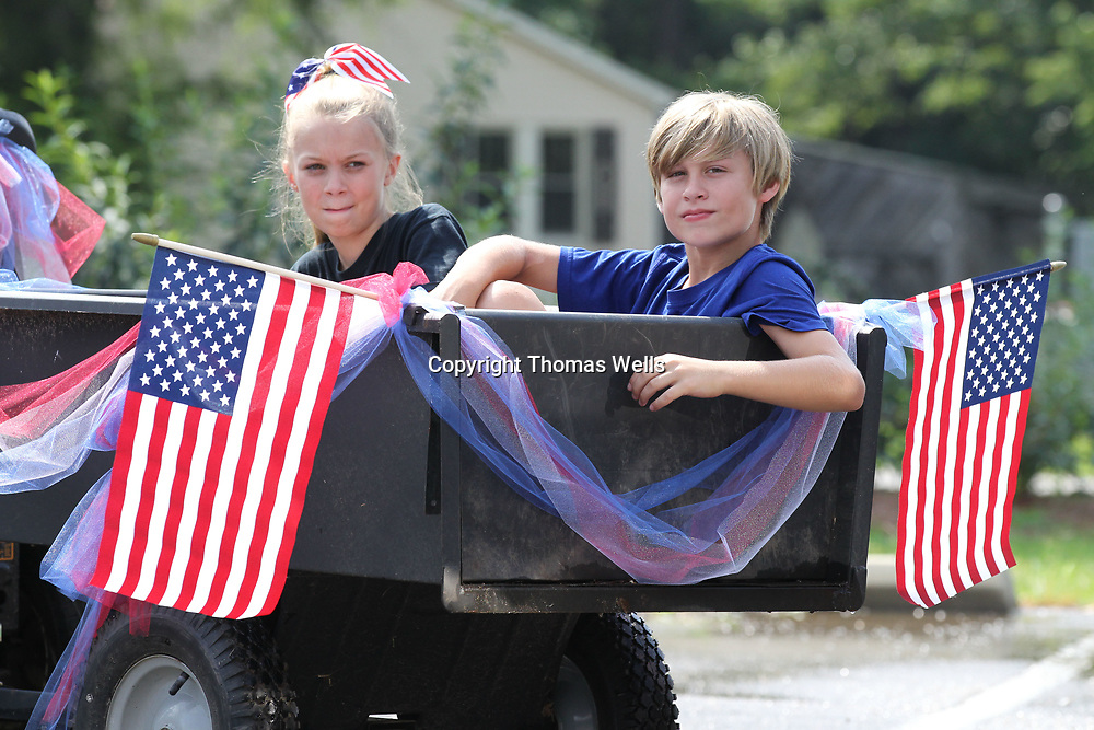Lindy Goin, 9, left, and her brother, Bryce, 10, sit in a trailer and wait for the Joyner parade to start.