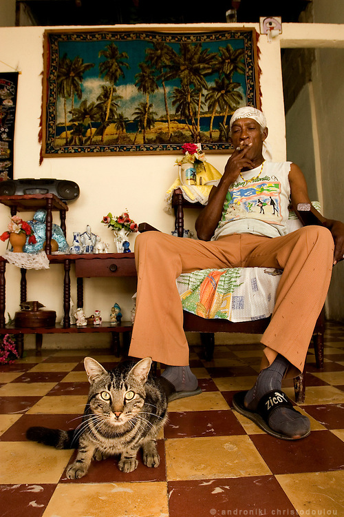 Walfredo is Walter's father and Walter describes him as a spiritual person, as he is a very dedicated Santeria believer . Here he is in his living-room in front of a Santeria doll smoking a Cuban cigar that is also used for Santeria ceremonies. Guanabakoa, Havana - CUBA
